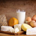 still life with dairy products, milk, eggs, bread and chees on a vintage wooden background